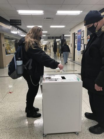 Student deposits their saliva sample in to the collection box.